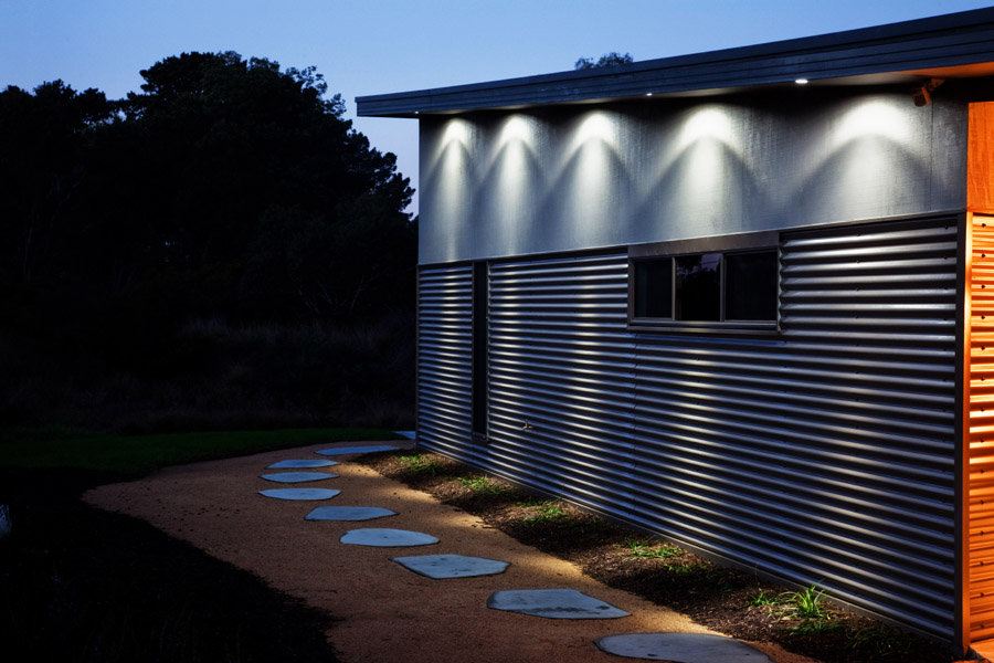 Side view of a house, with path running alongside. Downlights on exterior of building lighting path.